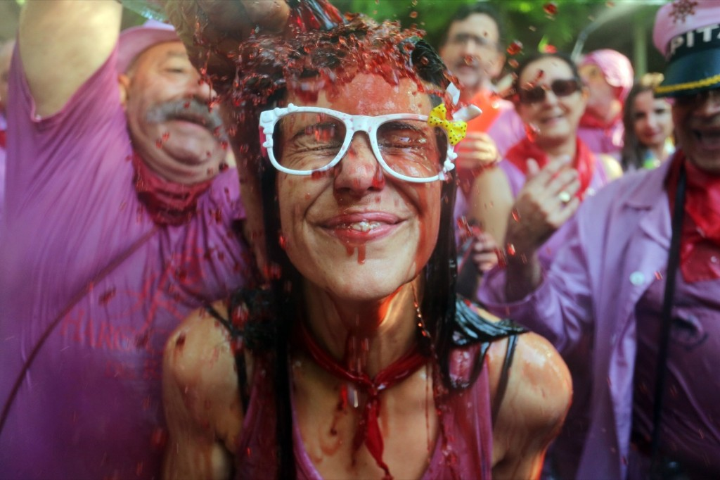"A man pours red wine on a girl's head during the""Batalla del Vino"" (Battle of Wine) in Haro, Spain. AFP PHOTO / CESAR MANSO"