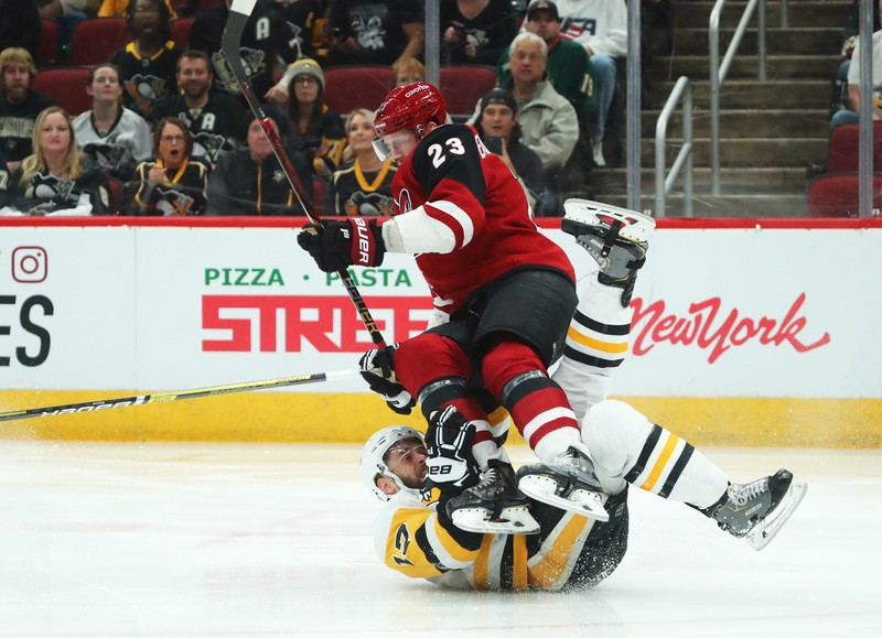 Jan 18, 2019; Glendale, AZ, USA; Arizona Coyotes defenseman Oliver Ekman-Larsson (23) top falls as he collides with Pittsburgh Penguins right wing Bryan Rust (17) in the first period at Gila River Arena. Mandatory Credit: Mark J. Rebilas-USA TODAY Sports