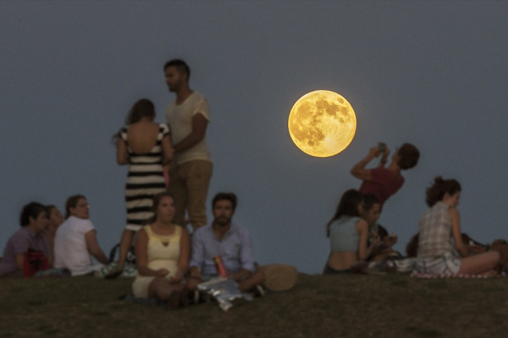 People gather in a park as a perigee moon, also known as a supermoon, rises in Madrid. AP Photo/Andres Kudacki