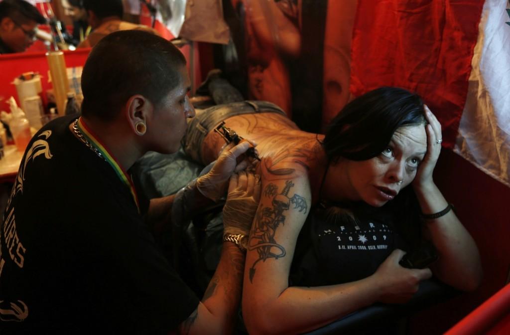 A woman is tattooed during the Art Tattoo Bolivia 2014 convention in La Paz. AP Photo/Juan Karita