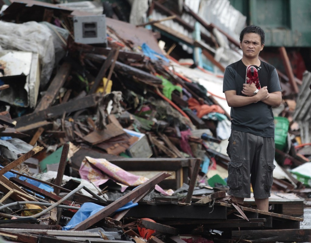 A resident amid damaged homes in Tacloban. The city remains littered with debris as many are without food, water and electricity. AP Photo/Aaron Favila