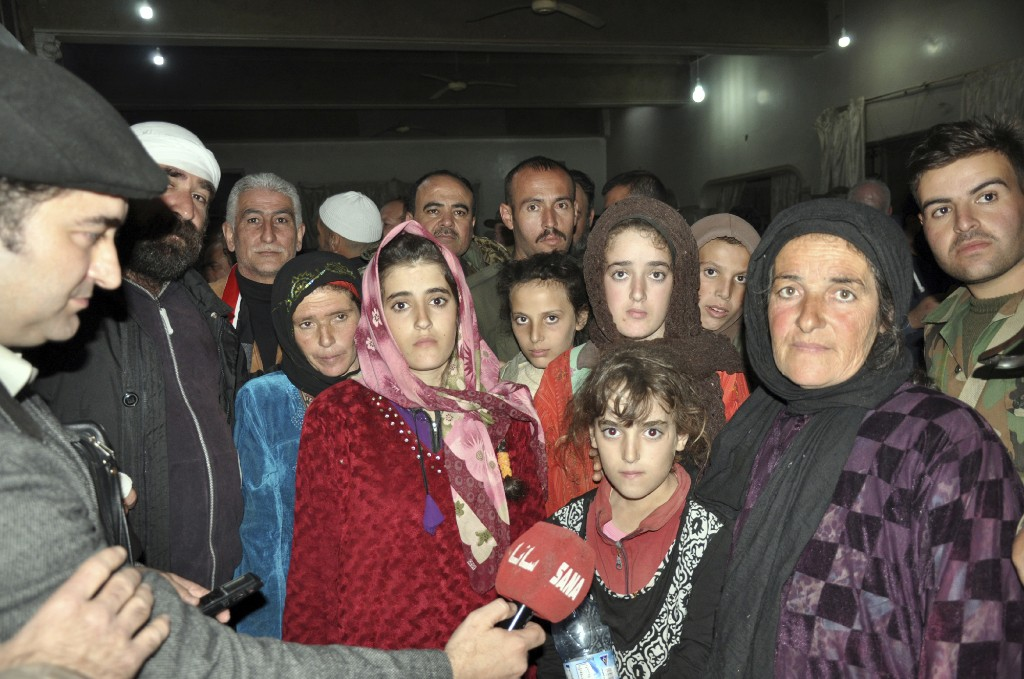 In this photo released by the Syrian official news agency SANA, women and children who were rescued from the Islamic State group in the Hamima area east of the historic town of Palmyra, after they arrived to the southern province of Sweida, Syria, Friday, Nov. 9, 2018. Islamic State group militants shot and killed two children during an operation to liberate a group of hostages from southern Syria that were being held by the extremist group since July, a father and activists said Friday. (SANA via AP)