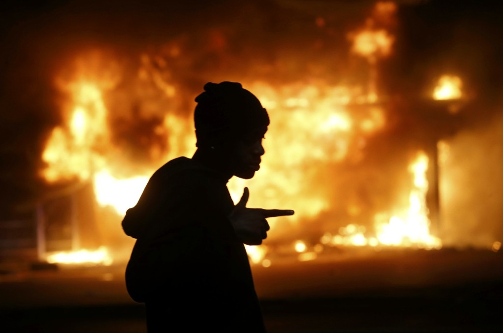 A man walks past a burning building during rioting after a grand jury returned no indictment in the shooting of Michael Brown in Ferguson. REUTERS/Jim Young