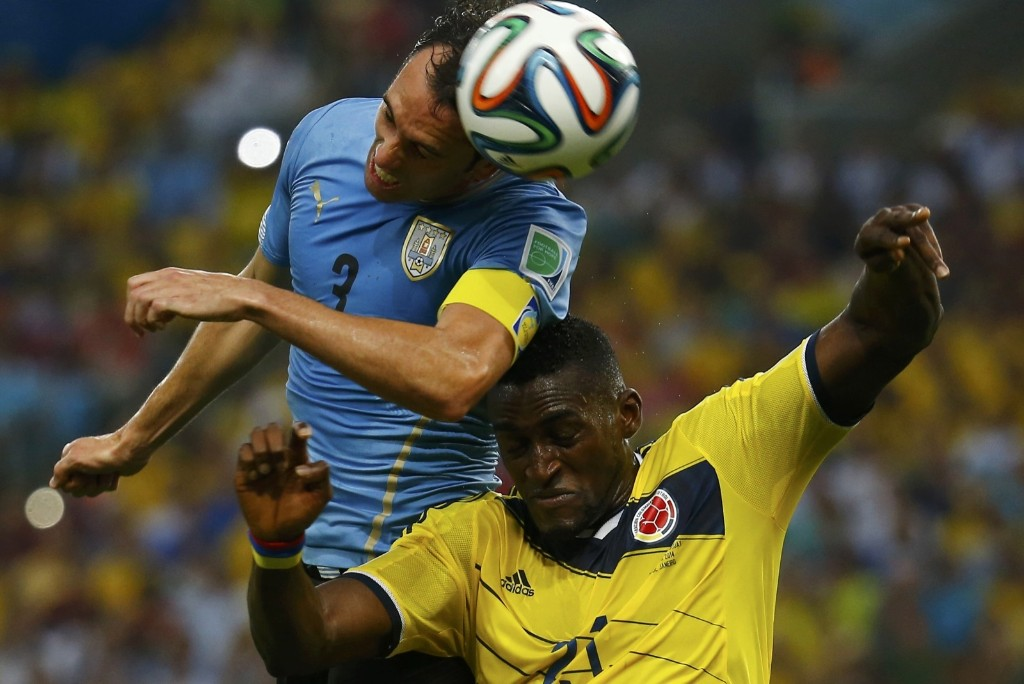 Uruguay's Diego Godin heading ball over Colombia's Jackson Martinez. REUTERS/Kai Pfaffenbach