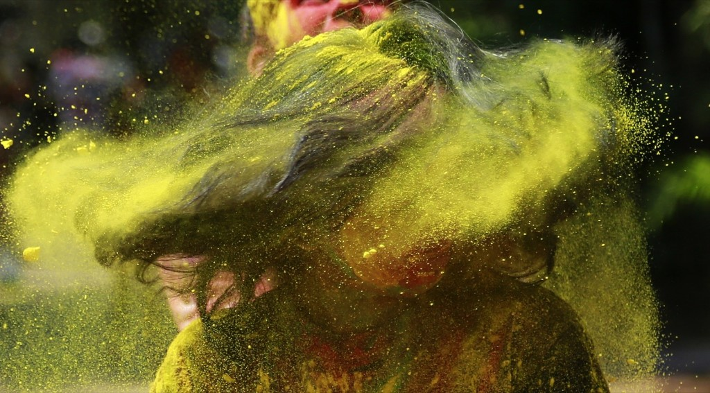 An Indian woman shakes her powder-covered head as she celebrates Holi, the Hindu festival of colors, in Mumbai. AP Photo/Rafiq Maqbool