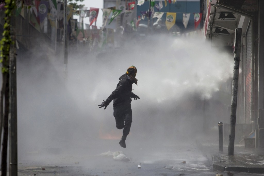 A masked protester runs away from a water cannon's jet during clashes with police in the Okmeydani neighbourhood of Istanbul. REUTERS/Kemal Aslan
