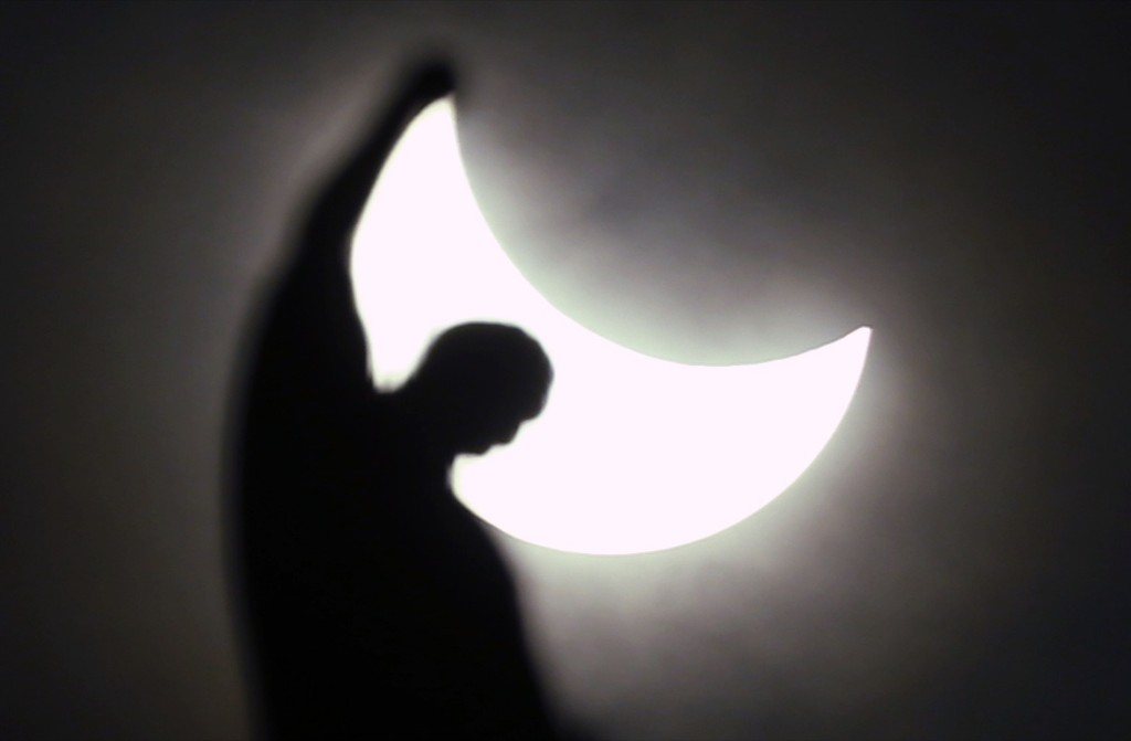 The moon starts to block the sun during a solar eclipse over a statue of the Duomo gothic cathedral in Milan. AP Photo/Luca Bruno