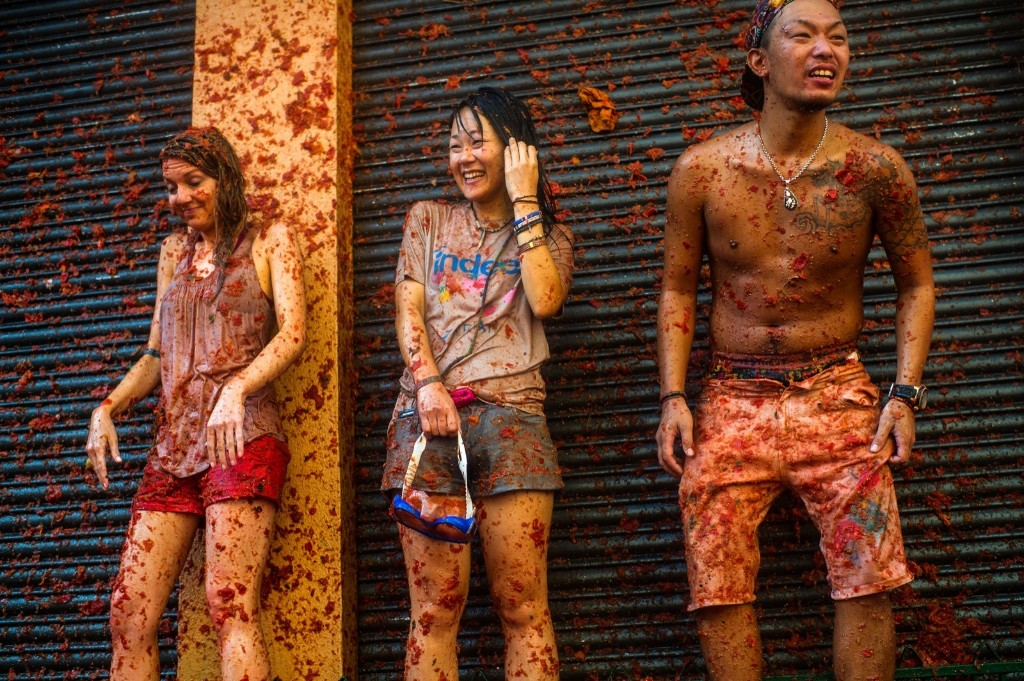 Revellers enjoy the atmosphere in tomato pulp while participating the annual Tomatina festival, Wednesday, in Bunol, Spain. David Ramos/Getty Images