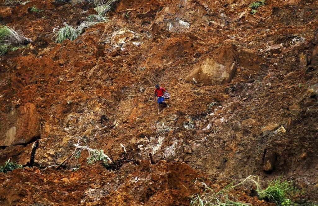 A man carrying a suitcase crosses a muddy slope at the site of a landslide at the Koslanda tea plantation near Haldummulla, Sri Lanka. REUTERS/Dinuka Liyanawatte