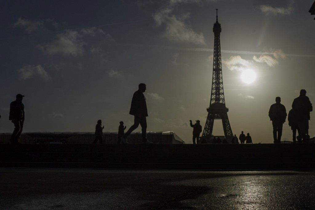 Tourists visit the site of Eiffel Tower which remained closed on the first of three days of national mourning in Paris, Sunday. AP Photo/Daniel Ochoa de Olza