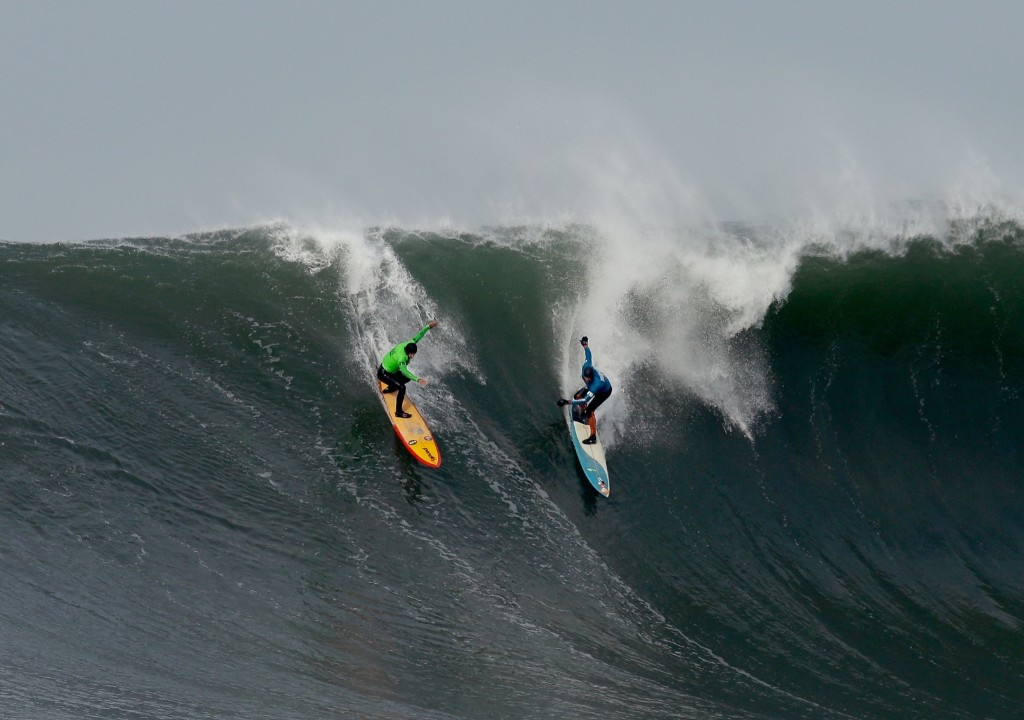 Danilo Couto, left, and Peter Mel share a wave during the second heat of round one at Mavericks. Ezra Shaw/Getty Images