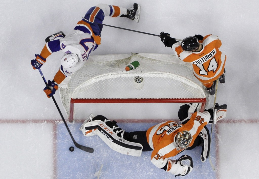 New York Islanders Anders Lee tries to score on Philadelphia Flyers goalie Steve Mason and Sean Couturier during game in Philadelphia. AP Photo/Matt Slocum