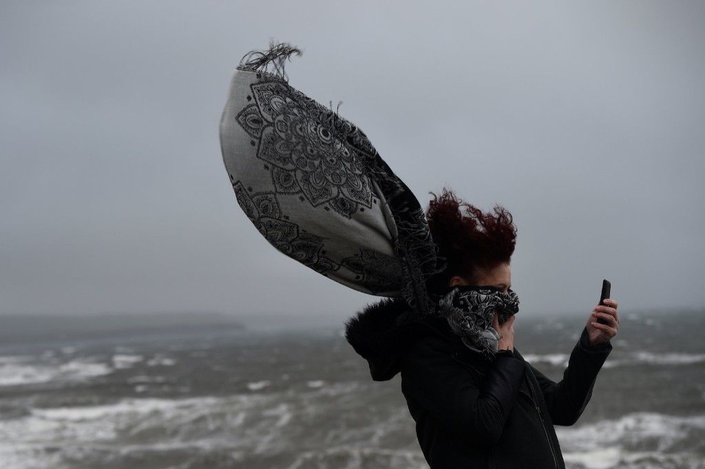 A woman takes a picture during storm Ophelia in the County Clare town of Lahinch, Ireland. REUTERS/Clodagh Kilcoyne