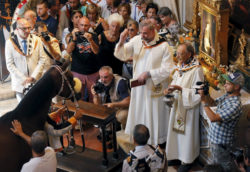 A priest blesses jockey Jonathan Bartoletti and his horse named Bened of the Lupa (Wolf) parish during a blessing ceremony in a church, before the Palio race in Siena August 17. REUTERS/Fabio Muzzi