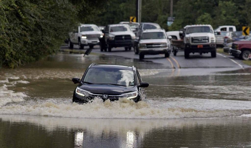 Motorists try to navigate deep water flowing over a road in Walker, La., Monday. AP Photo/Max Becherer