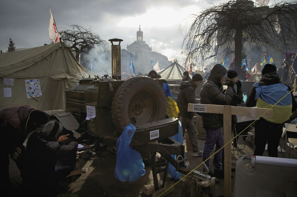 Protesters stand next to their tent camp in Kiev, Ukraine, Thursday. Several thousand activists kept up the demonstrations and besieged government meetings. AP Photo/Ivan Sekretarev