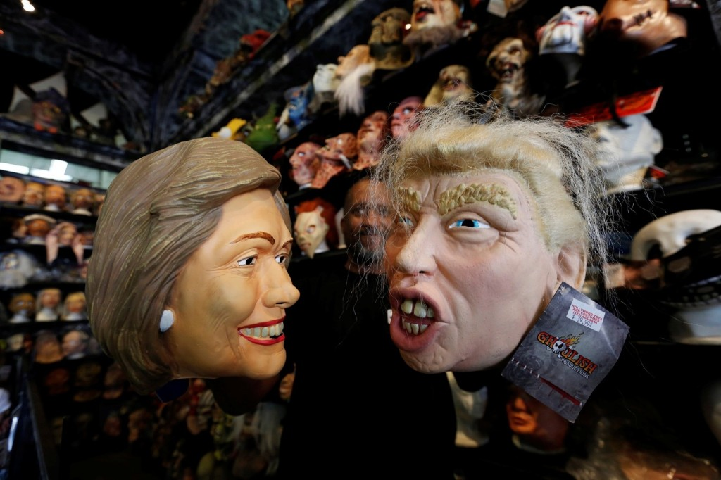 An employee holds up masks depicting Hillary Clinton and Donald Trump at Hollywood Toys & Costumes in Los Angeles. REUTERS/Mario Anzuoni