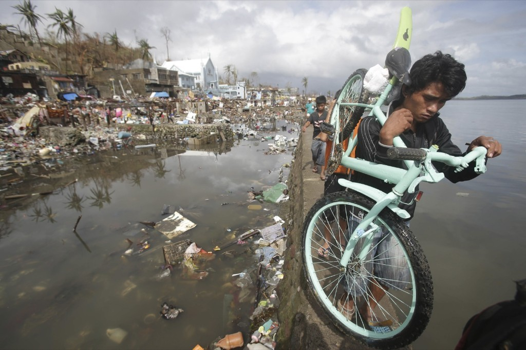 A resident carries his bicycle past houses that were destroyed in Tacloban. AP Photo/Aaron Favila