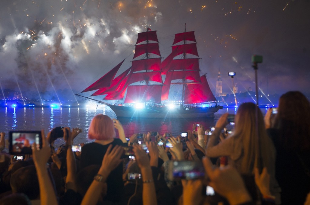 People watch a brig with scarlet sails on the Neva River during festivities marking school graduation in St. Petersburg, Russia. AP Photo/Dmitri Lovetsky