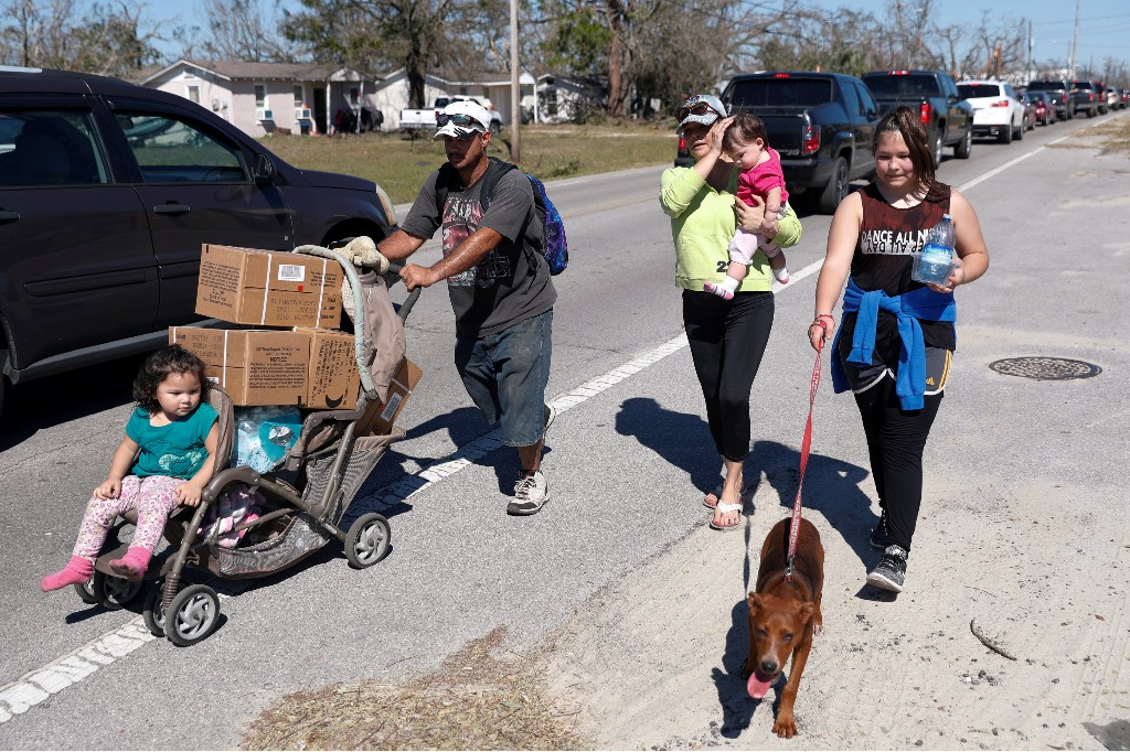 Lazaro and Amanda Perez, of Callaway, walk home with their children after picking up food and water from a public distribution location in Parker, Florida, U.S., October 13, 2018. REUTERS/Terray Sylvester