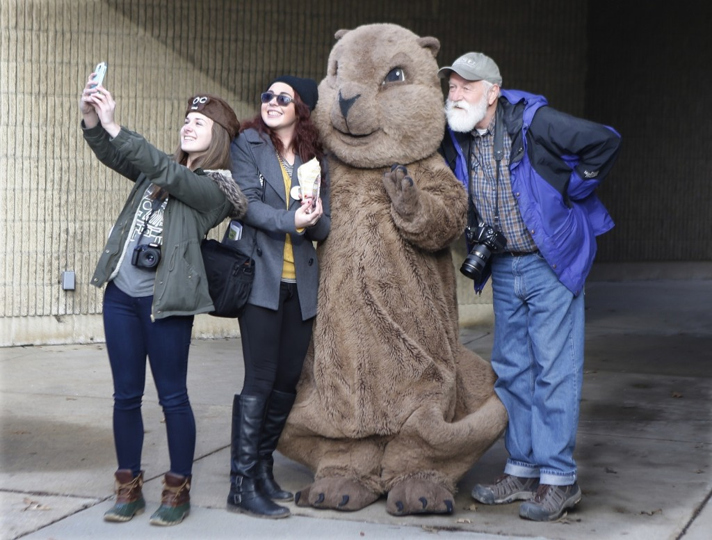 """A group of visitors pose for pictures and take selfies with the """"Punxsutawney Phil"""" mascot. AP Photo/Keith Srakocic"""