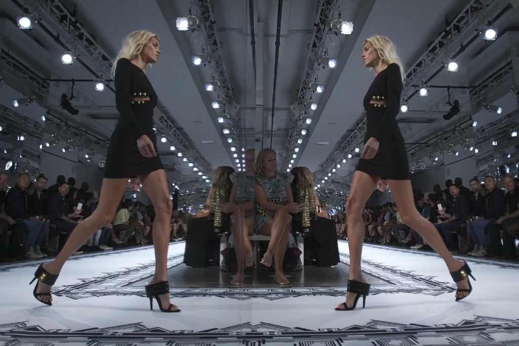 A model is reflected in a mirror as she presents a creation at the Versus Versace Spring/Summer 2015 show during New York Fashion Week. REUTERS/Carlo Allegri