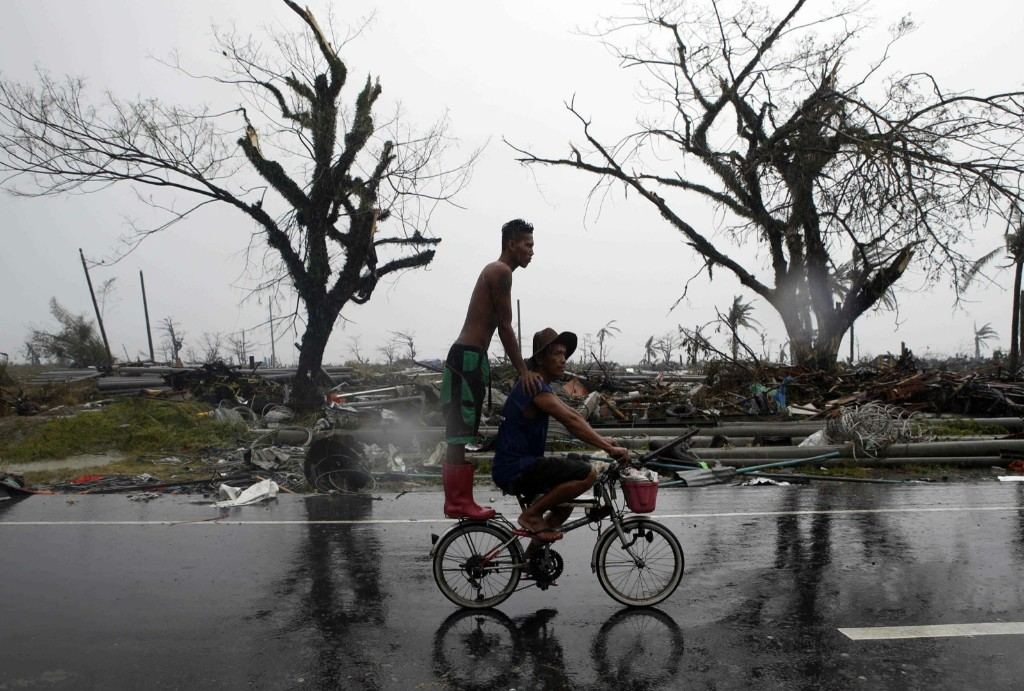 Residents ride a bicycle past a road lined with debris. Typhoon Haiyan destroyed about 70 to 80 percent of the area in its path as it tore through the province. REUTERS/Erik De Castro
