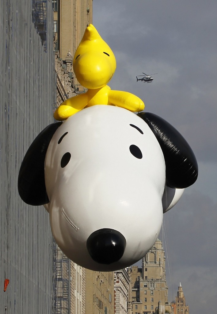 The Snoopy and Woodstock balloon floats down Central Park West as a police helicopter hovers in the sky during the Macy's Thanksgiving Day Parade in New York, Thursday. Photo by Gary Hershorn