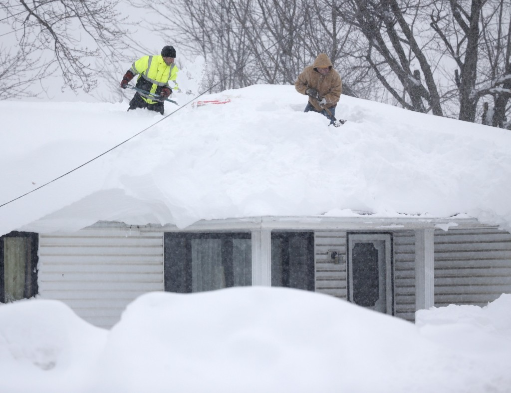 Mark Settlemyer gets help clearing snow from the roof of his mother's house from Ken Wesley on Wednesday in Lancaster, New York. AP Photo/Mike Groll