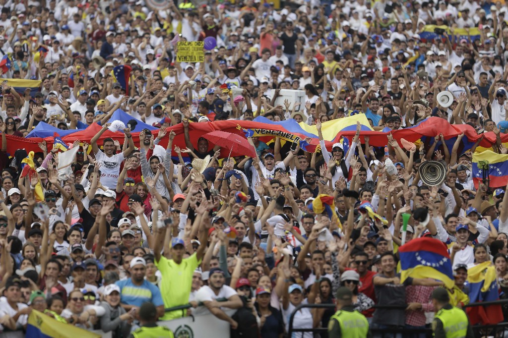 People begin to fill the Venezuela Aid Live concert on the Colombian side of the Tienditas International Bridge on the outskirts of Cucuta, Colombia, on the border with Venezuela, Friday, Feb. 22, 2019. Venezuela's power struggle is set to convert into a battle of the bands Friday when musicians demanding Nicolas Maduro allow in humanitarian aid and those supporting the embattled leader's refusal sing in rival concerts being held at both sides of a border bridge where tons of donated food and medicine are being stored. (AP Photo/Fernando Vergara)