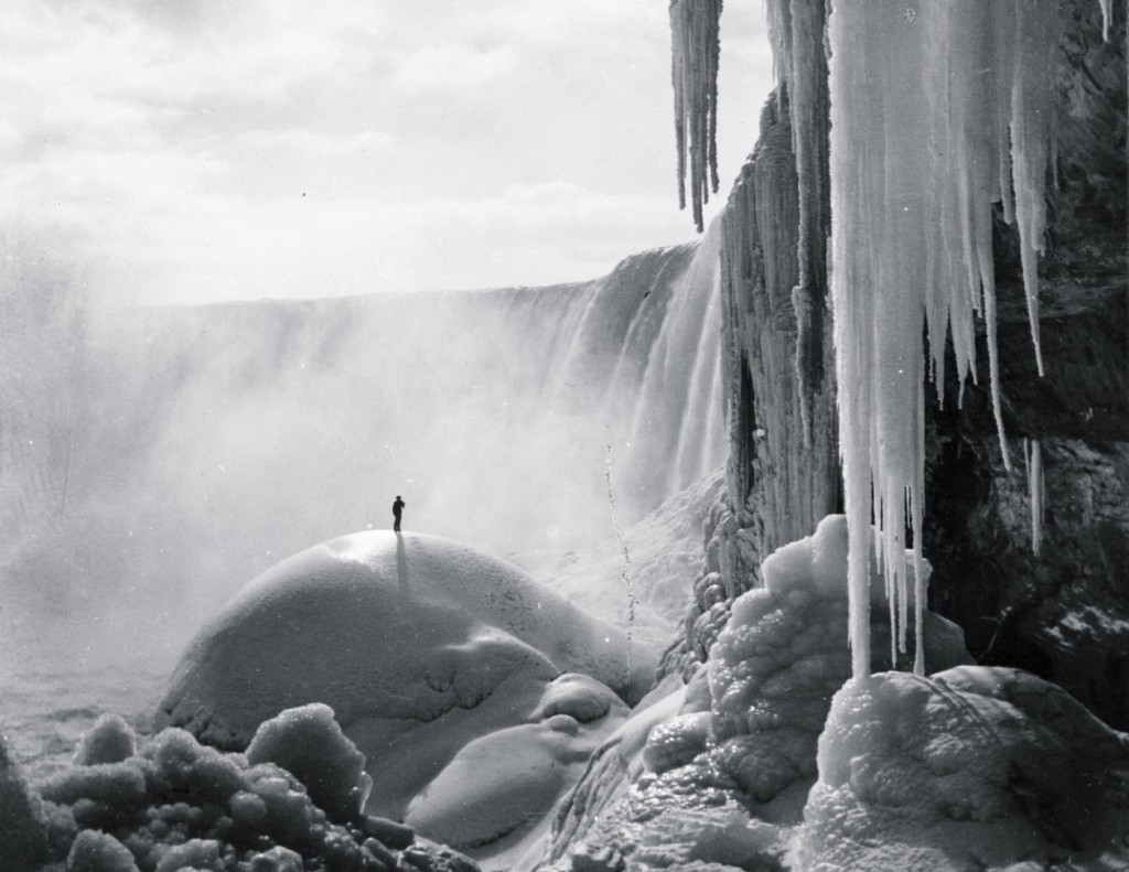A sole adventurer stands on an ice dome beneath the icicled Niagara Falls in a frozen wonderland, circa 1903. Buyenlarge/Getty Images