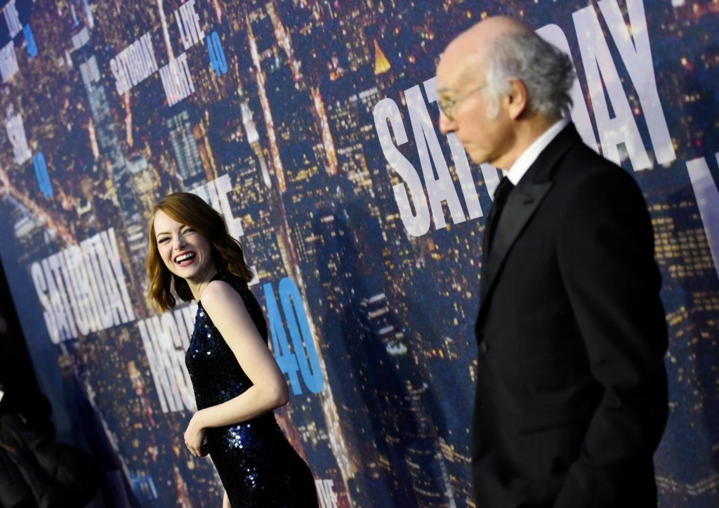 Actress Emma Stone laughs at Larry David on the red carpet at the SNL 40th Anniversary Special,Sunday, in New York. Evan Agostini/Invision/AP