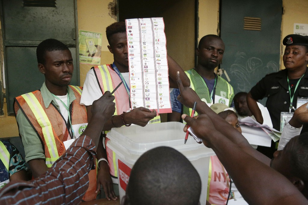 Party agents argue with electoral commission officials on a ballots the claim it was valid for the presidential race after the Gwadabawa polling station closed in Yola, Nigeria, Saturday Feb. 23, 2019. Incumbent President Muhammadu Buhari is facing opposition presidential candidate Atiku Abubakar in the presidential election. (AP Photo/Sunday Alamba)