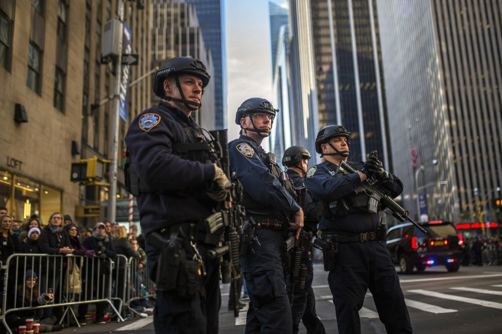 Police stand guard as people watch the Macy's Thanksgiving Day Parade in New York, Thursday. AP Photo/Andres Kudacki