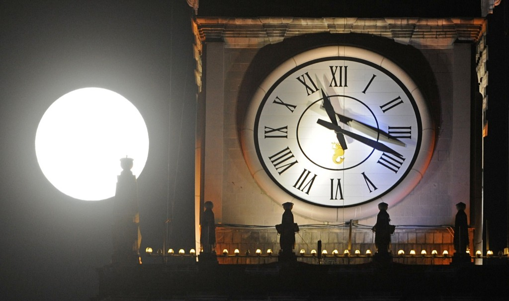 Supermoon rises next to a clock on top of the Palace of Culture in Warsaw. AP Photo/Alik Keplicz