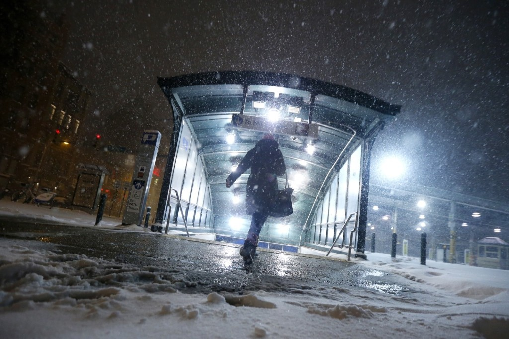 A commuter walks into the Hoboken PATH train station during a snowstorm, Saturday. AP Photo/Julio Cortez