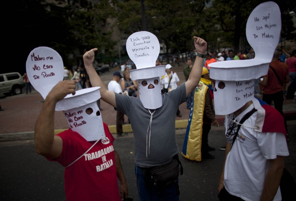 Opposition members, their faces covered with masks simulating a toilet, protesting against Venezuela's President Nicolas Maduro in Caracas. AP Photo/Ariana Cubillos