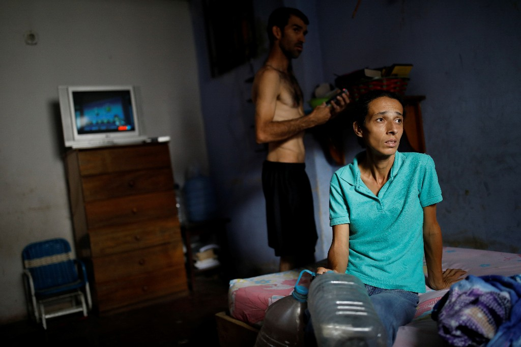 Yaneidi Guzman, 38, sits on her mother-in-law's bed as her husband, Jorge Perez, stands behind her in Caracas, Venezuela, March 31, 2018. REUTERS/Carlos Garcia Rawlins