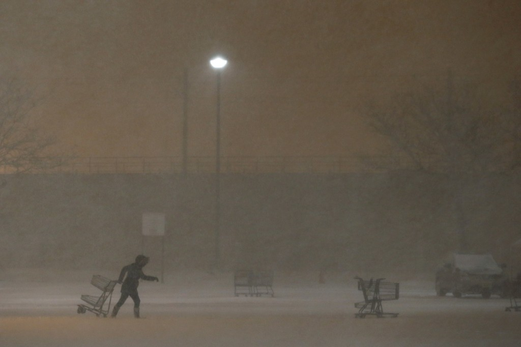 A grocery store employee collects shopping carts from a parking lot during a snowstorm, Saturday, in Jersey City, N.J. AP Photo/Julio Cortez