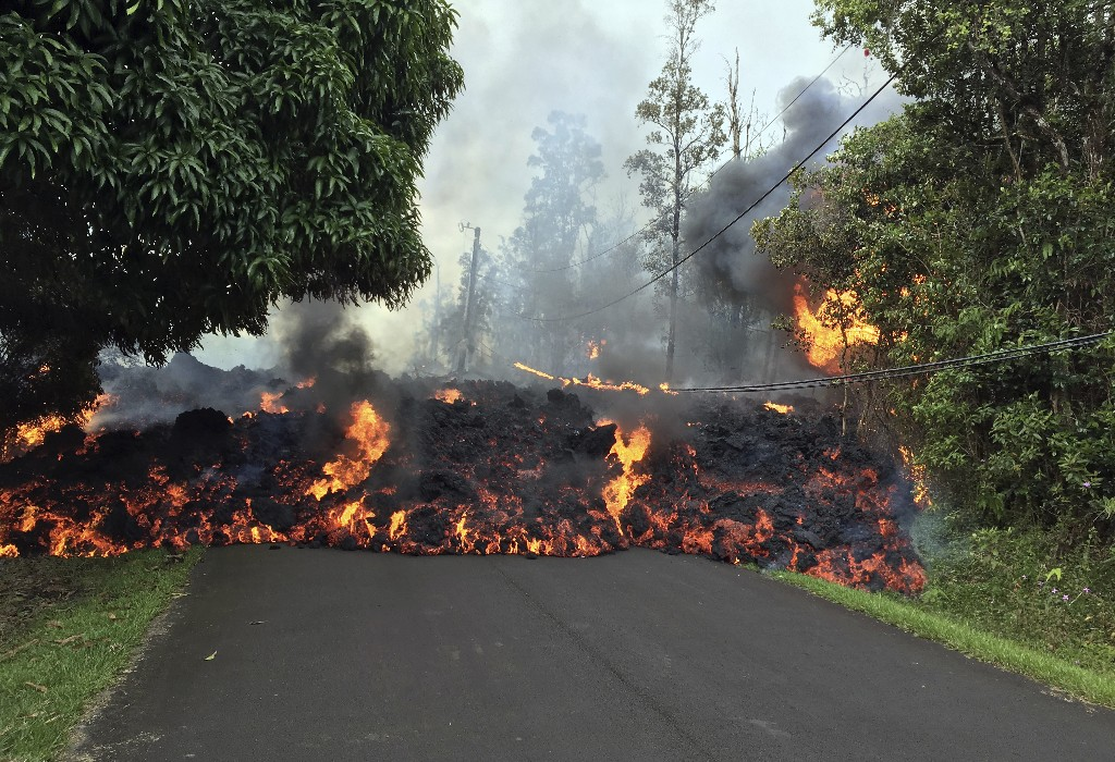 In this Sunday, May 6, 2018 photo provided by the U.S. Geological Survey, a lava flow moves across Makamae Street in the Leilani Estates subdivision near Pahoa on the island of Hawaii. Kilauea volcano has destroyed more than two dozen homes since it began spewing lava hundreds of feet into the air last week, and residents who evacuated don't know how long they might be displaced. The decimated homes were in the Leilani Estates subdivision, where molten rock, toxic gas and steam have been bursting through openings in the ground created by the volcano. (U.S. Geological Survey via AP)