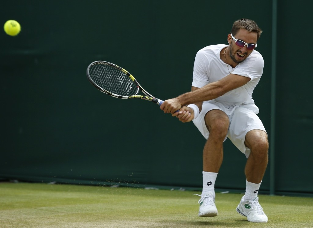 Viktor Troicki of Serbia returns a ball to Vasek Pospisil of Canada. AP Photo/Alastair Grant