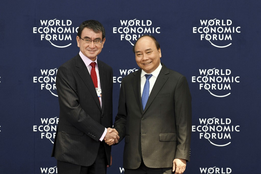 Japan's Foreign Minister Taro Kono, left, shakes hands with Vietnamese Prime Minister Nguyen Xuan Phuc during the welcoming ceremony of the World Economic Forum on ASEAN at the National Convention Center in Hanoi, Vietnam Wednesday, Sept. 12, 2018. (Ye Aung Thu/Pool Photo via AP)