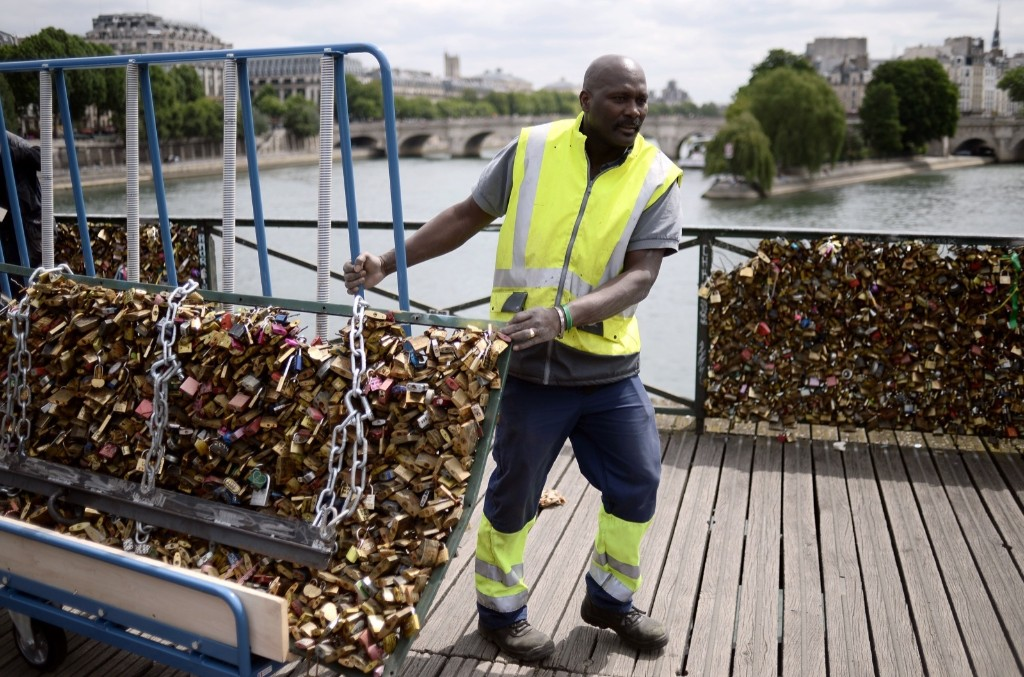 """A worker removes """"love padlocks"""" attached on the railings of the Pont des Arts bridge in Paris, Monday. Stephane de Sakutin/AFP/Getty Images"""