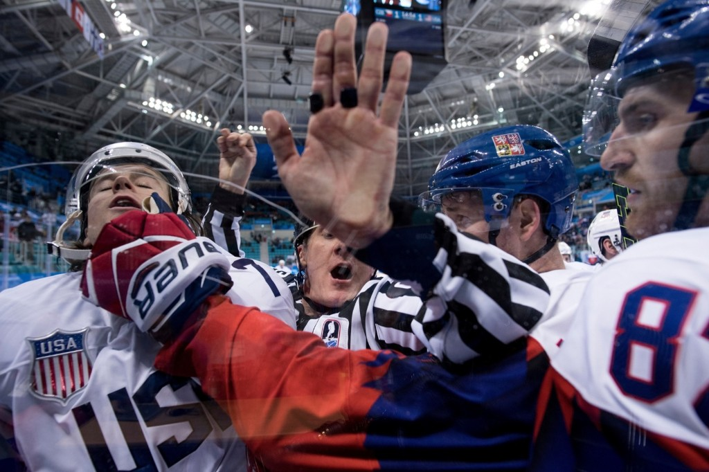 John Mccarthy of the U.S. is pinned against the glass after receiving a penalty during the men's quarterfinals game against the Czech Republic. BRENDAN SMIALOWSKI/AFP/Getty Images