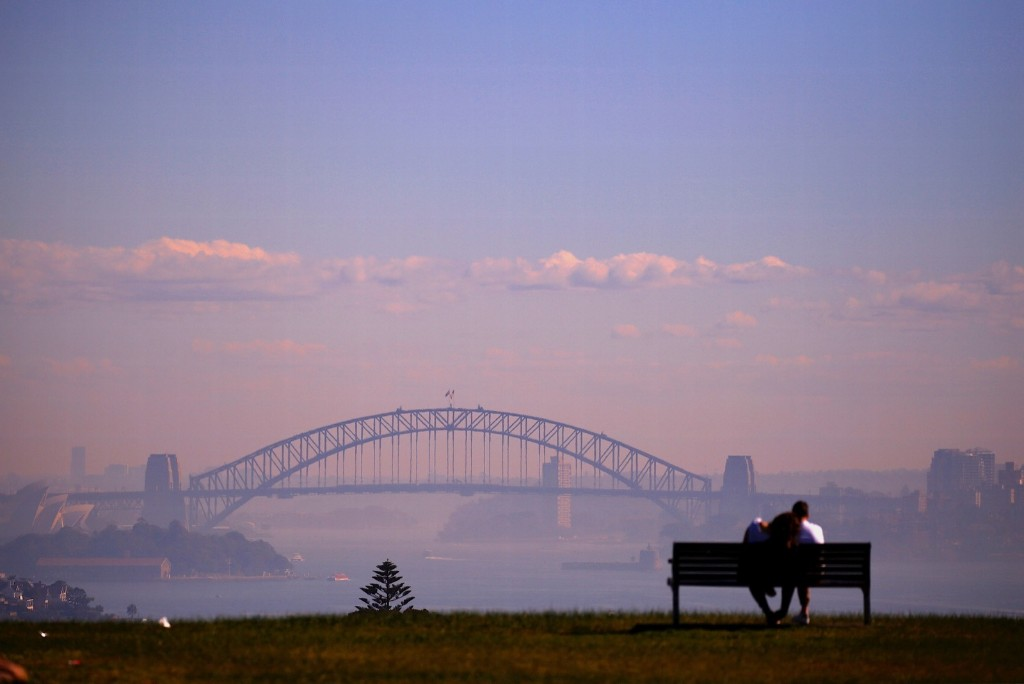 A couple sits on a seat overlooking Sydney Harbour which was covered in smoke from hazard reduction burns in nearby bushland. REUTERS/David Gray