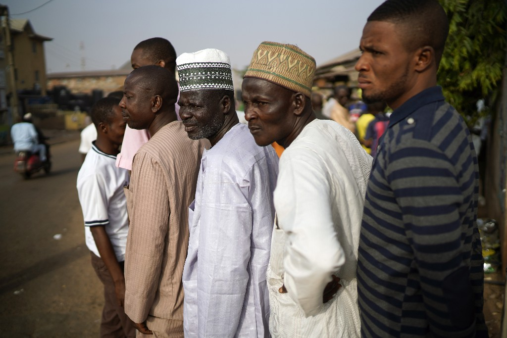 Nigerian men line up to cast their vote in Kaduna, Nigeria, Saturday, Feb. 23, 2019. Incumbent President Muhammadu Buhari is to face opposition presidential candidate Atiku Abubakar in the presidential election. (AP Photo/Jerome Delay)