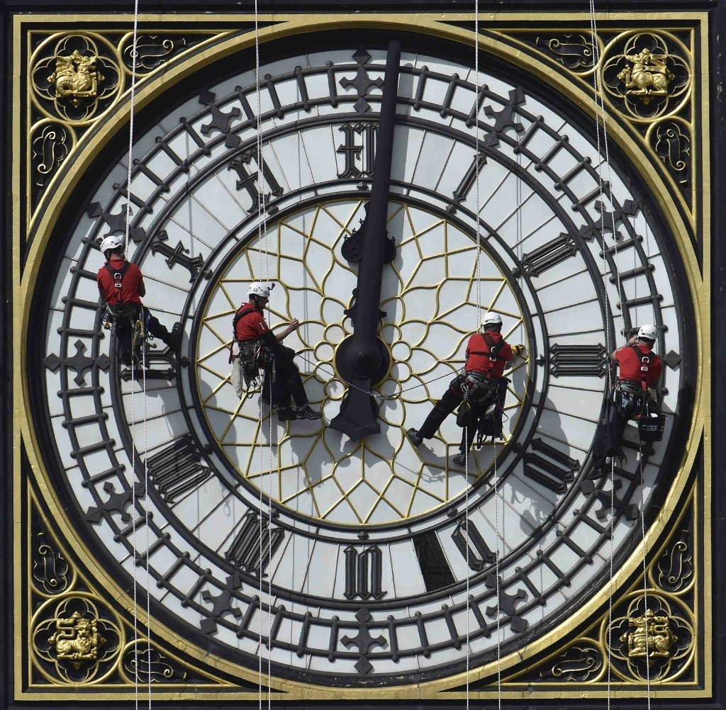 Cleaners abseil down one of the faces of Big Ben to clean and polish the clock face. REUTERS/Toby Melville