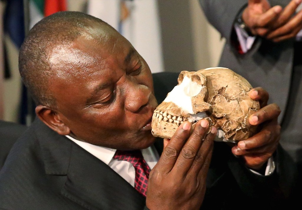 """South Africa's Deputy President Cyril Ramaphosa kisses a replica of the skull of a newly discovered ancient species, named """"Homo naledi"""", during its unveiling outside Johannesburg, Thursday. REUTERS/Siphiwe Sibeko"""