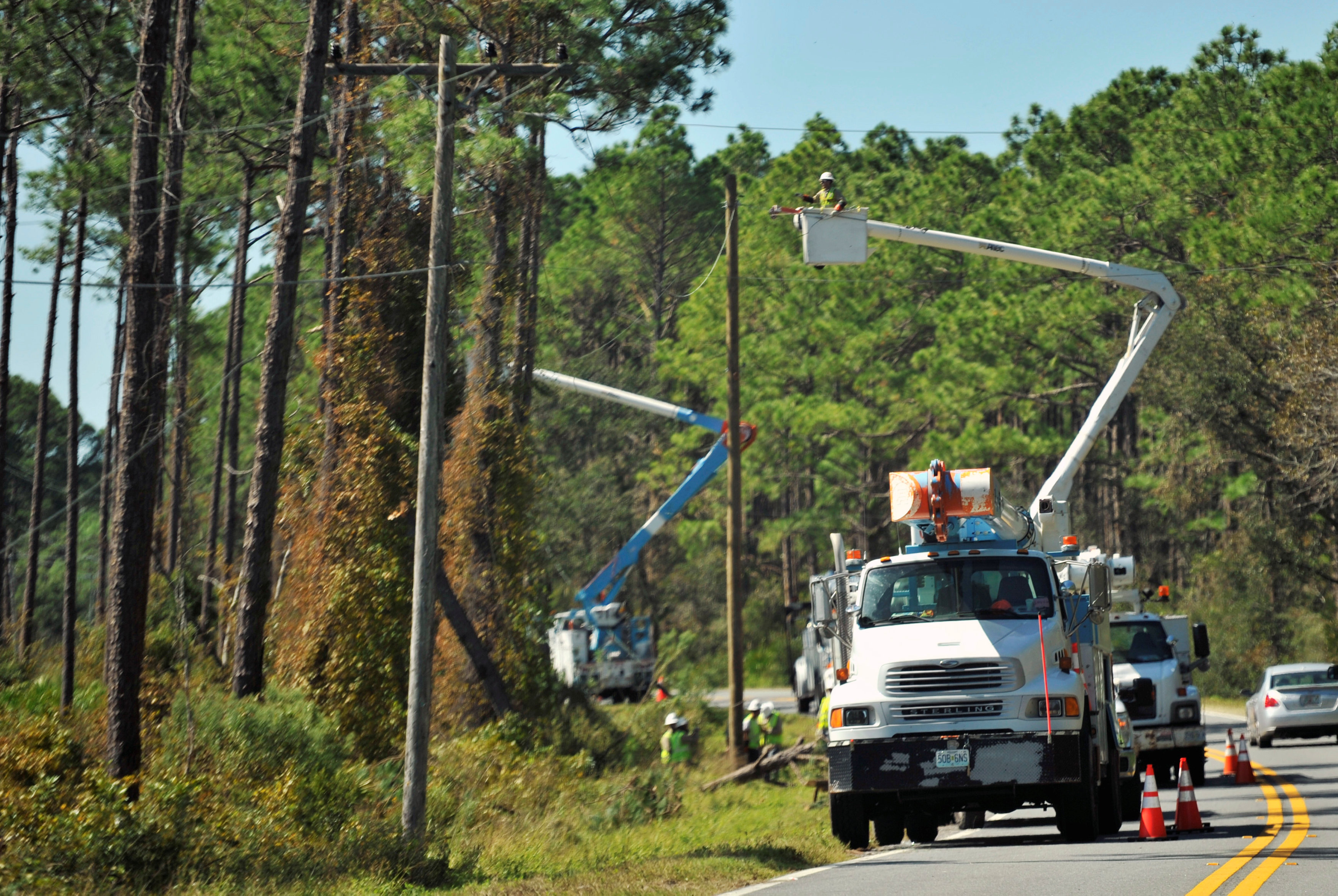 Utility workers repair power lines on U.S. Highway 98 near Alligator Point in the aftermath of Hurricane Michael in Franklin County, Florida, U.S., October 13, 2018. REUTERS/Steve Nesius
