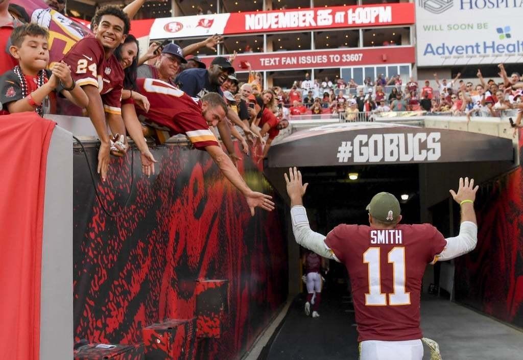 Washington Redskins quarterback Alex Smith celebrates with fans as he runs off the field. (Jonathan Newton/The Washington Post)